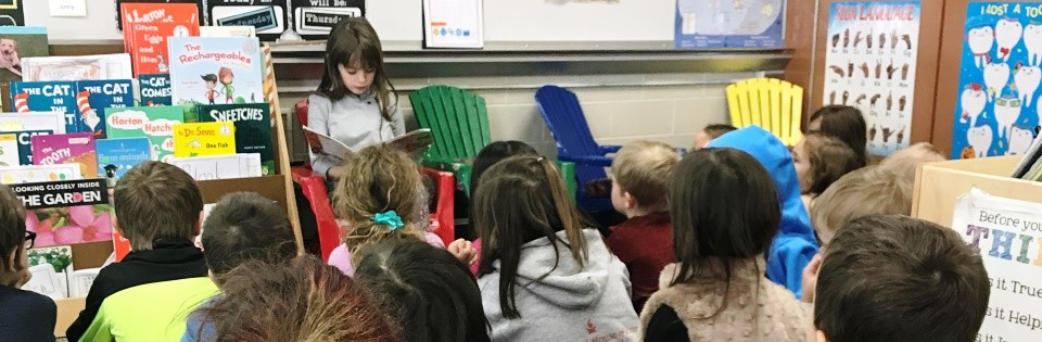 Girl reading to Kindergarten class