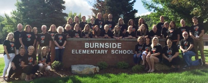 Burnside staff outside by sign.